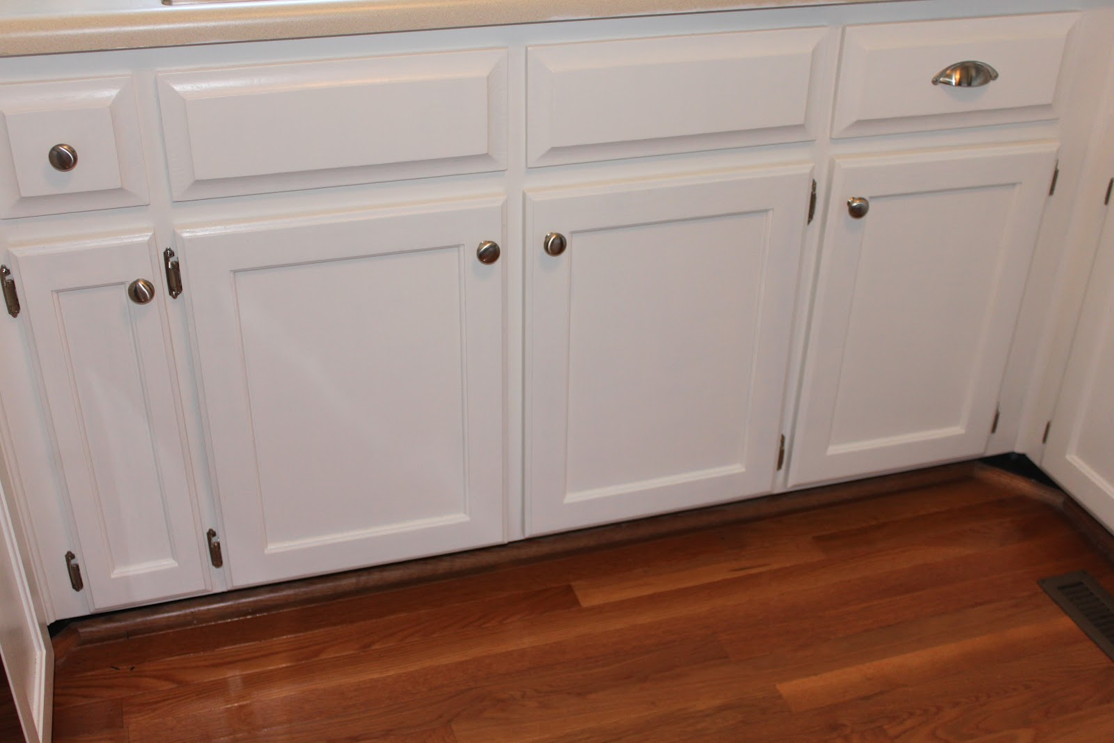 I think the white cabinets look much better with our wood floors.