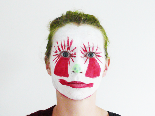A white and red face painted face with green sprayed hair on a white background.