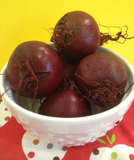 Organic red beets in a white bowl