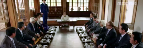 Lee Gun speaks at his family meeting to two rows of executives.