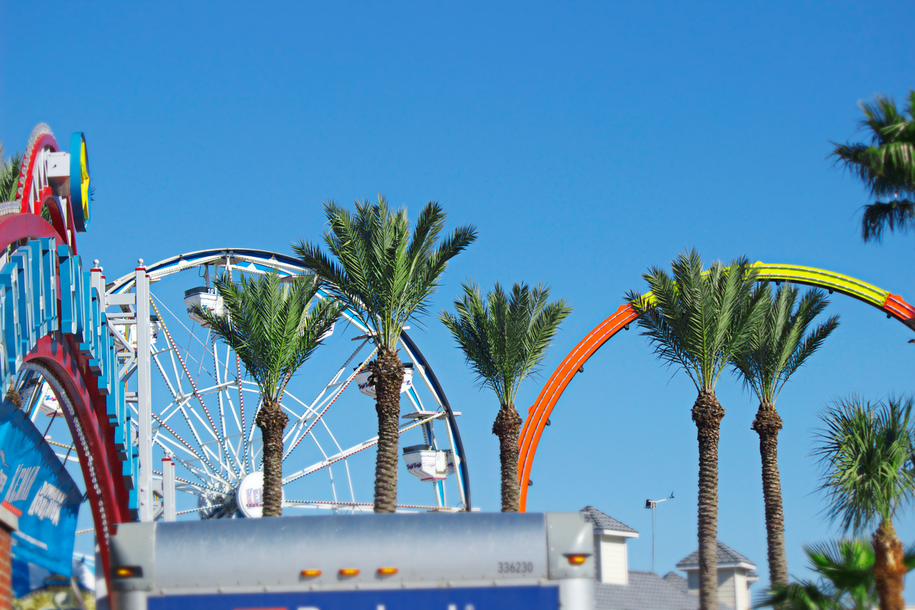 carnival boardwalk entrance with palm trees