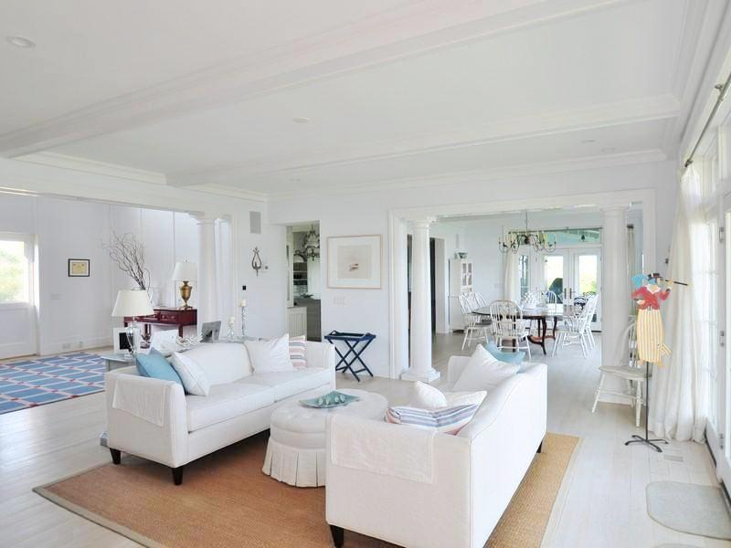 White living room with sea grass rug, dueling sofas, a white oval upholstered ottoman and a coffered ceiling