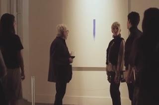 artista explicando su obra una raya azul en la pared