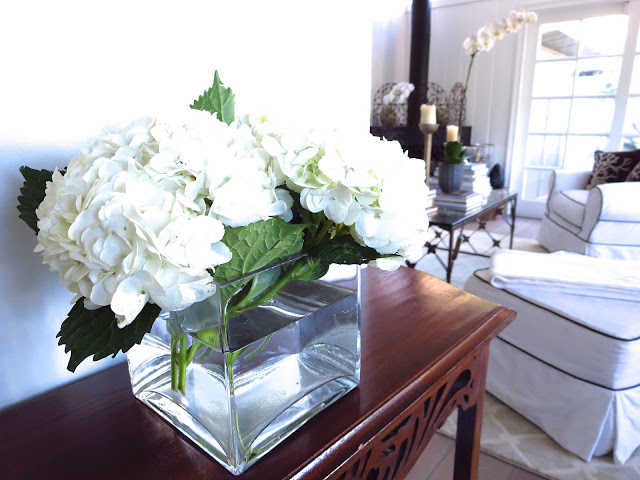 White hydrangeas on a wood side table in Coco of COCOCOZY's living room