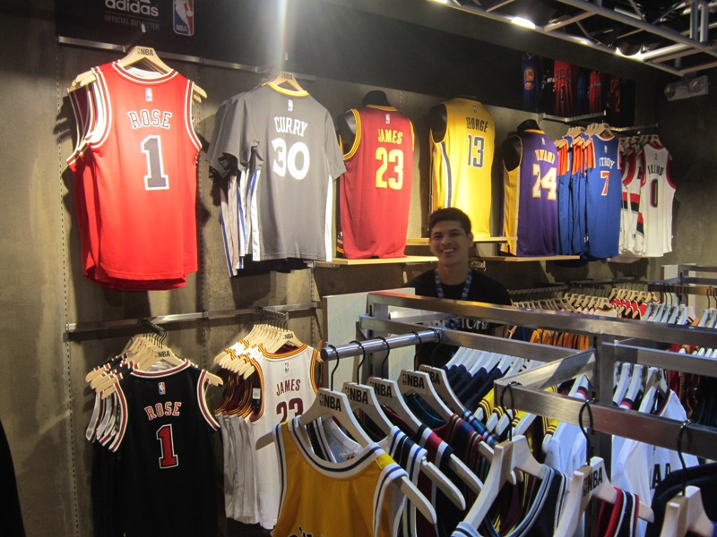 The flagship NBA Store is officially open. At this hall of hoops, ballers can salute their favorite teams with scads of NBA and WNBA merchandise. Guys can sport the same style of warm-up suits and sneakers worn by superstars like Steph Curry, LeBron James, and Kobe Bryant.