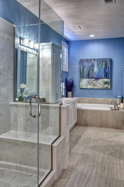 stylish modern bathroom with marble shower box, wood floors, and beautiful lavender flower