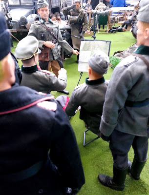 Group of 1/6 scale German soldiers being briefed in a diorama of an army post on display at a scale model exhibition.