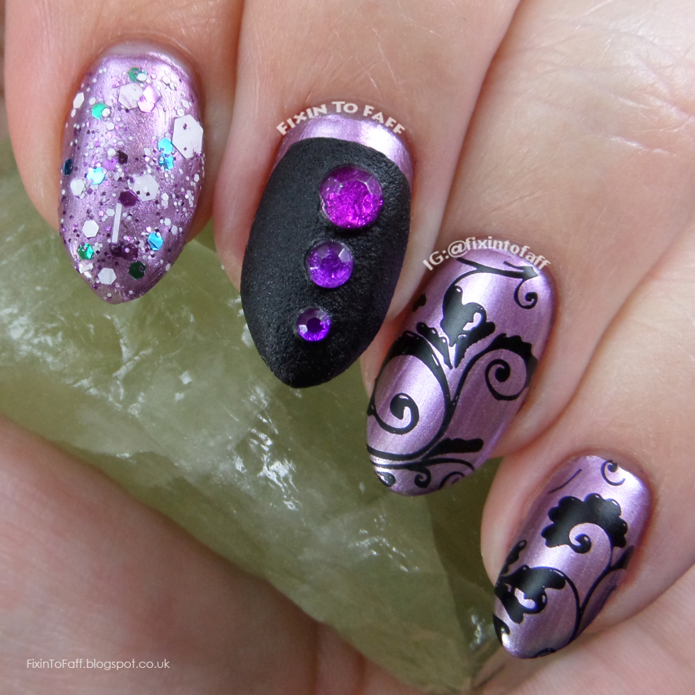 Nail art featuring stamping, glitter, texture, and rhinestones over chrome polish in purple and black tones.