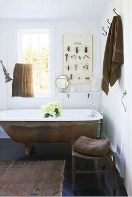 master bathroom with stand alone copper tub, dark wood floors, white walls, a small table used to hold towels, a window and poster with different insects