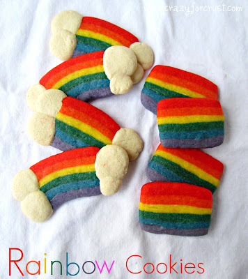 sugar cookies dyed rainbow colors with white clouds at ends on white linen with words
