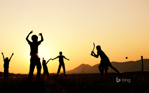 Silhouette of young Indian boys playing cricket