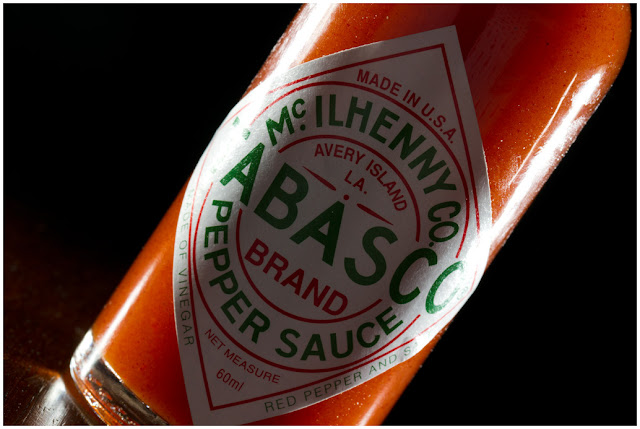 A photograph of a back-lit bottle of Tabasco Sauce
