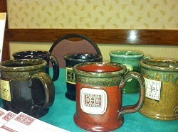 Table with green tablecloth displaying handmade ceramic coffee mugs painted brown, mustard, dark blue and green.