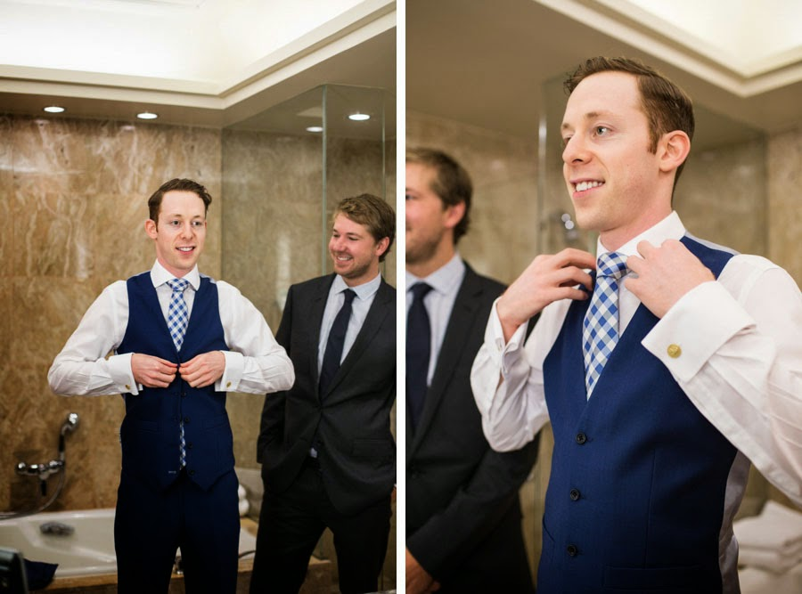 Groom getting ready, buttoning vest and fixing collar. Custom blue suit and blue checked tie. NYC Lifestyle wedding photography by Cassie Castellaw. www.cassiecastellaw.com