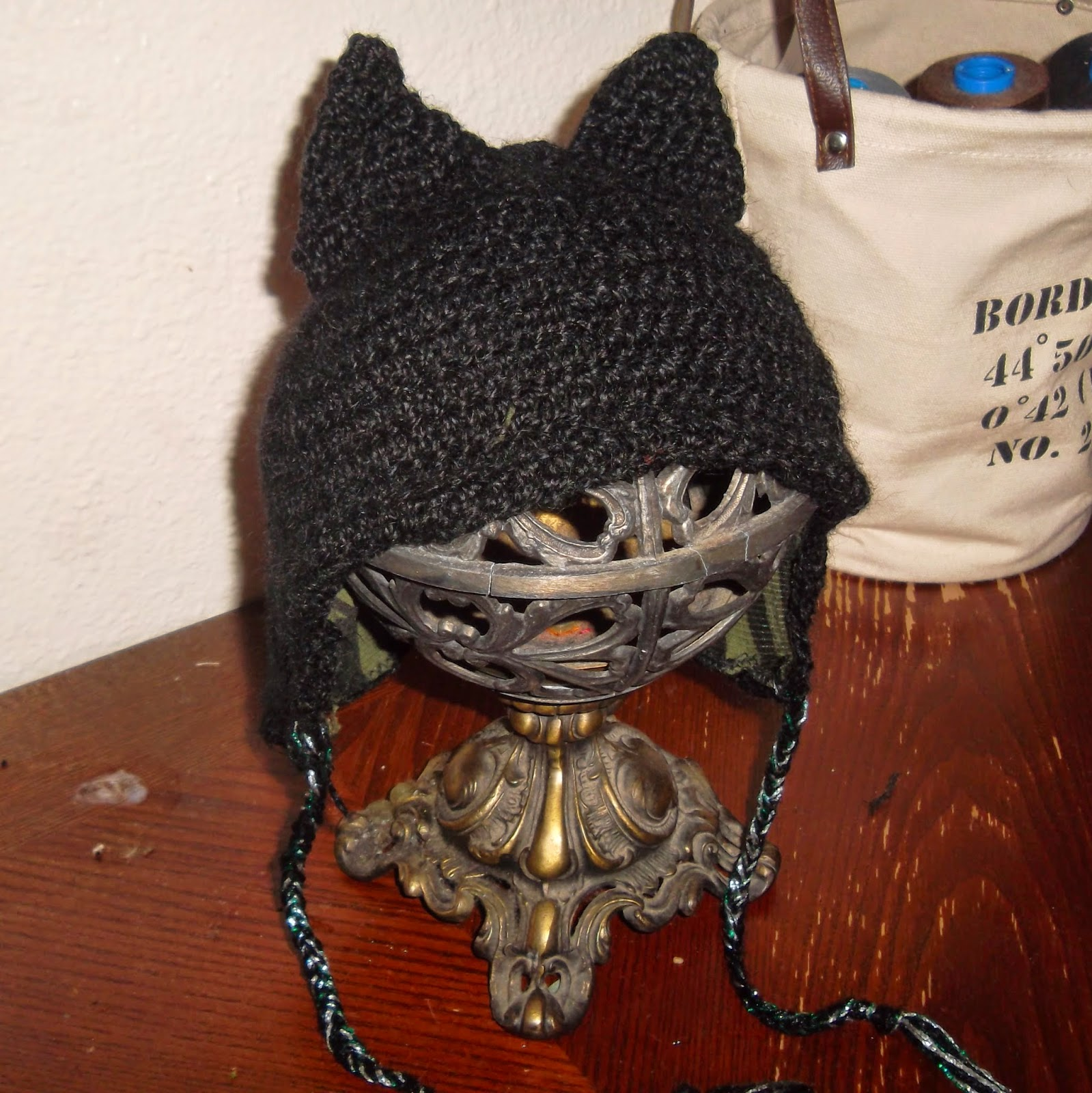 Beanie-style crocheted cap with cat ears, draped over openwork, globe-shaped metal stand.