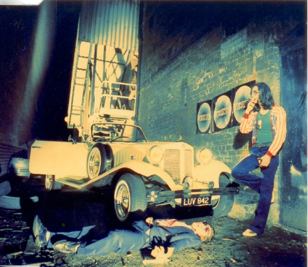Richard Ashcroft with long hair and a cigarette standing next to a car. Band the Verve's A Storm In Heaven album artwork