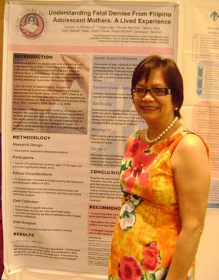 Ms. Borromeo with the winning poster piece of Prof. Timmy Agustin of Centro Escolar University