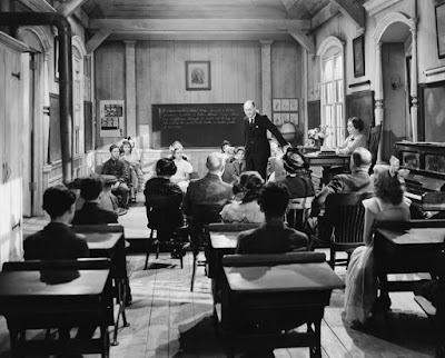 a teacher addresses students in an old-fashioned classroom from the last century