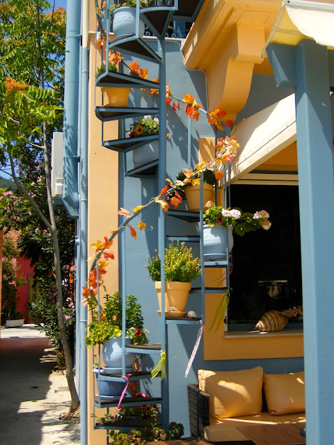 Spiral stair with flowerpots on colourful building | Architecture in the town of Fiskardo, Kefalonia, Greece