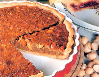 Treacle Macadamia Tart: A classic tart of macadamia nuts in a spicy molasses (treacle) base baked in a shortcrust shell shown with a wedge removed