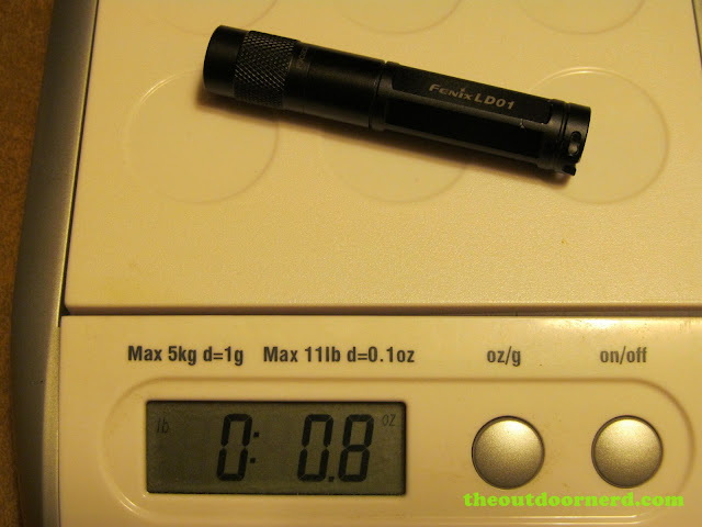 Fenix LD01 AAA Flashlight, shown on scale