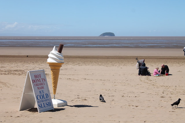 Weston Super Mare Beach scene with plastic ice cream and hot donuts stand