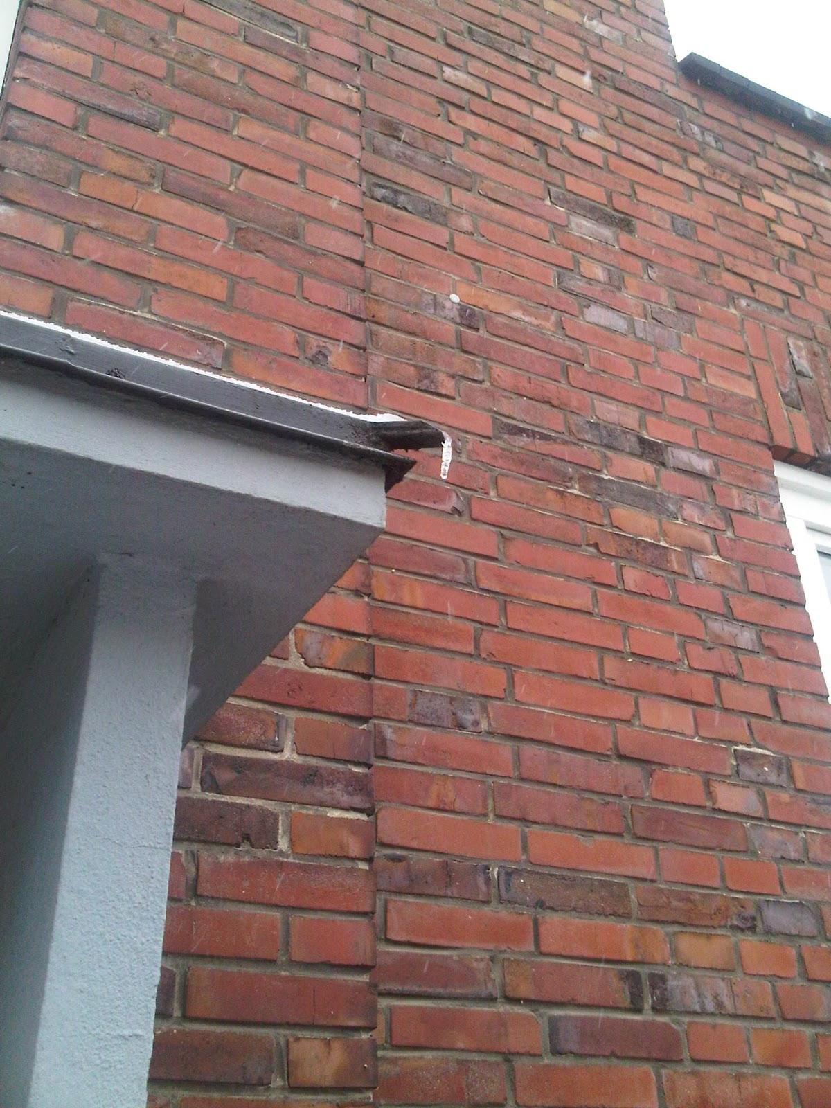 Vordach eines Wohnhauses mit Regenablauf, daran hängt ein Eiszapfen.