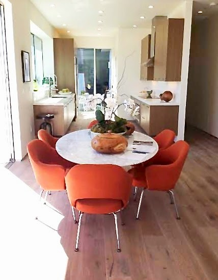 Dining room with modern bright orange chairs