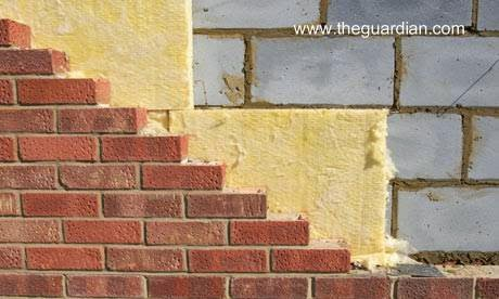 Muro de bloques de concreto con capa de material aislante y terminación de ladrillos