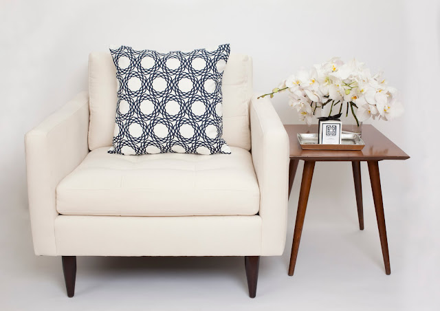 Nbaynadamas pillow on a white armchair next to a wooden table holding orchids and a Nbaynadamas candle