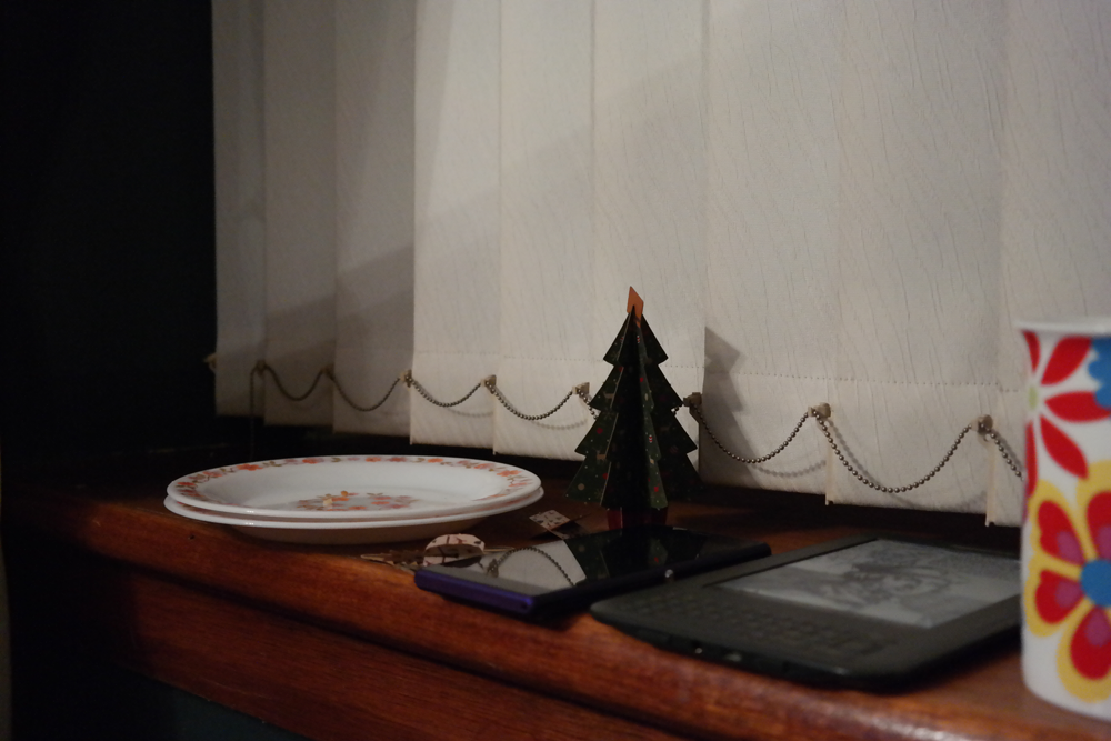 Dishes, phone, Kindle and cardboard Christmas tree