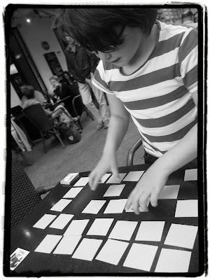Kind spielt Memory (schwarz-weiß-Aufnahme)