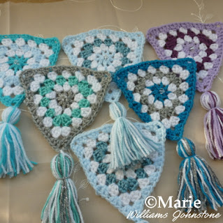 Cool winter colors of crocheted granny triangles and tassels