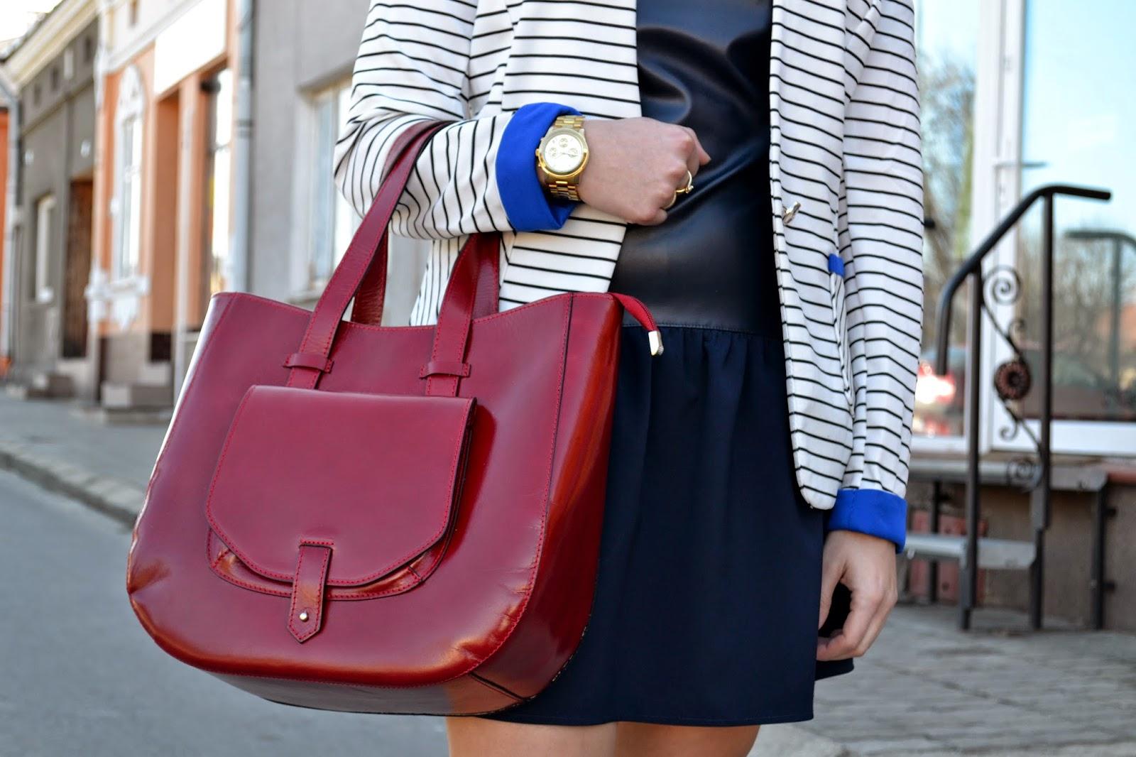złoty zegarek Michael Kors, czerwona torebka, granatowa sukienka