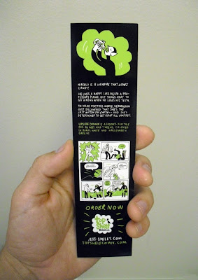 "Hand holding GotPrint printed green and black bookmark, ""upside down"" comic book"