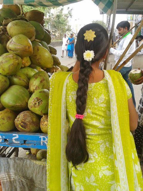Homely Tamil Nadu girl at coconut shop with long hair braid.