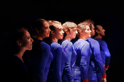 Seven people in purple-blue leotards lined up against a black background