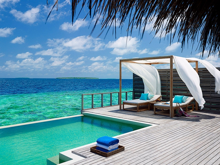 Deck with swimming pool and bed in Luxury Dusit Thani Resort in Maldives