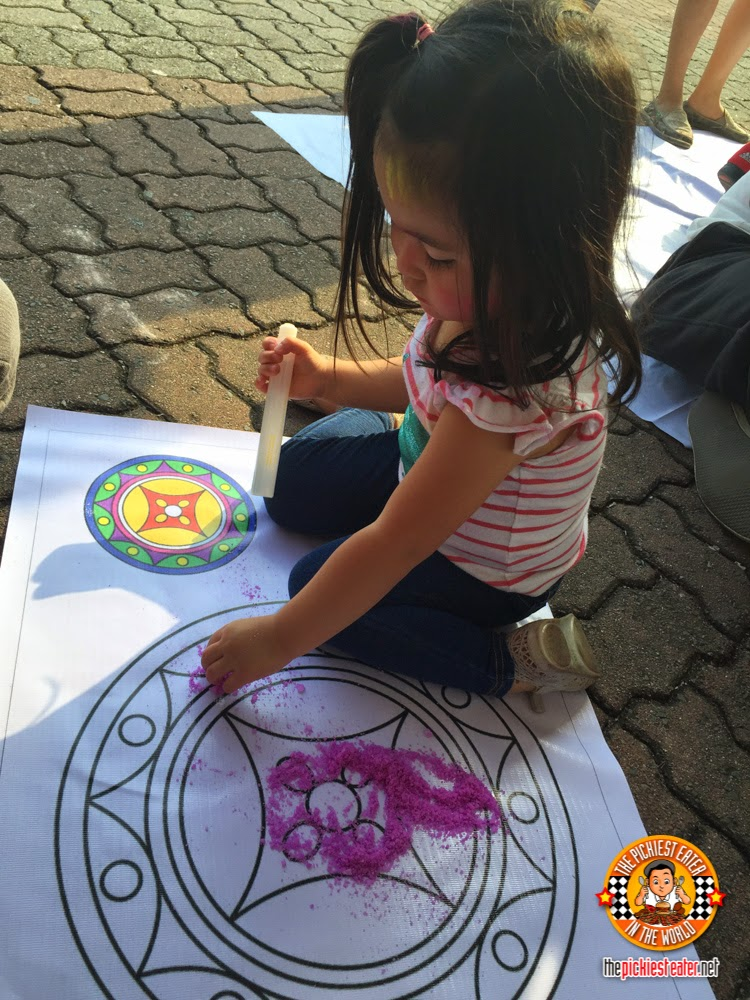 toddler making Rangoli