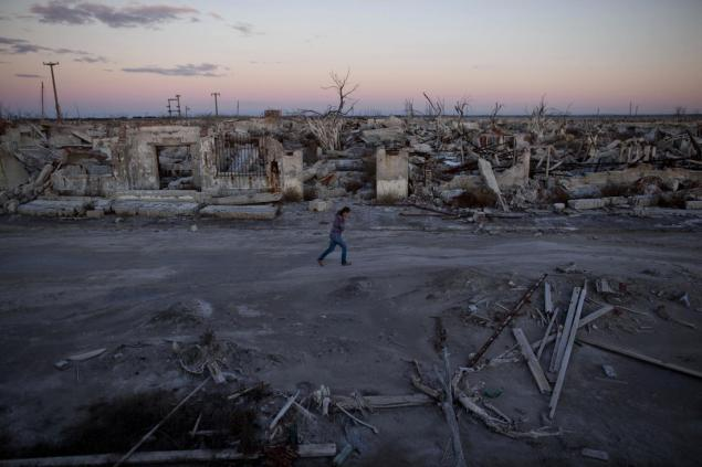 Former resident and tourist guide Norma Berg walks by a street in Epecuen. People come to see the rusted hulks of automobiles and furniture, crumbled homes and broken appliances.
