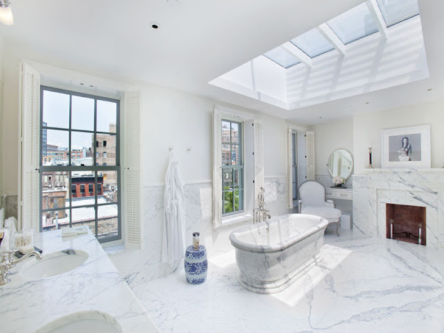 master bathroom with a marble bathtub and fireplace, encasement windows with views of the Highline and a skylight