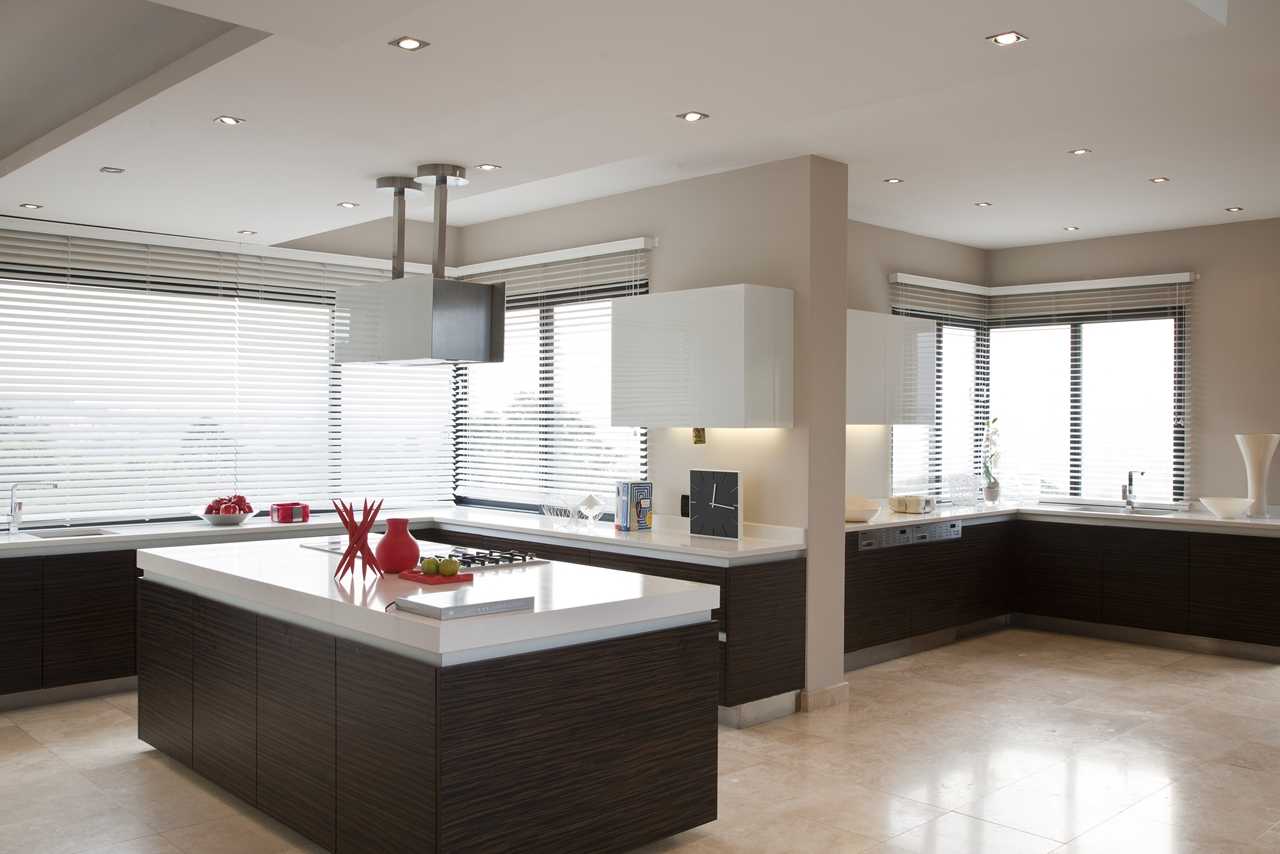 picture of large modern kitchen with brown wooden furniture and marble surfaces