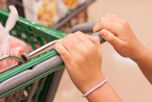 child's hands pushing shopping cart