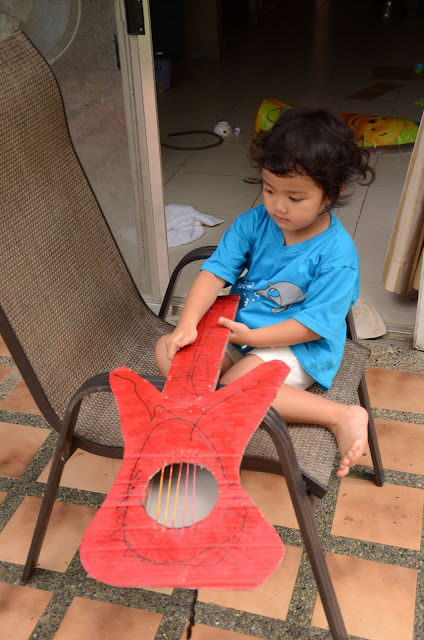 showing off her red cardboard guitar