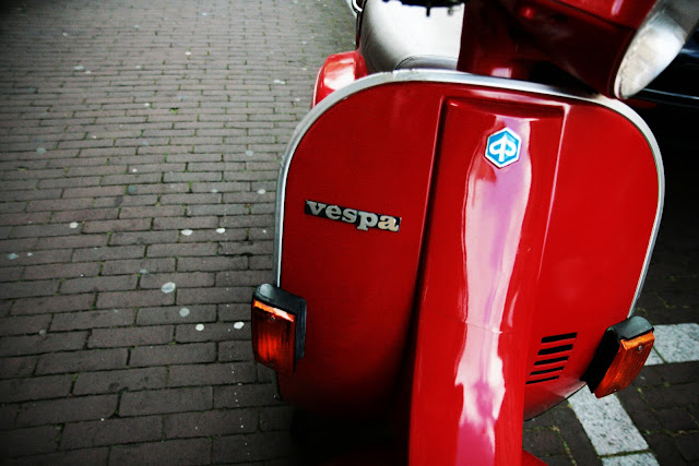 A very shiny, red Vespa to scooter Amsterdam, Holland.
