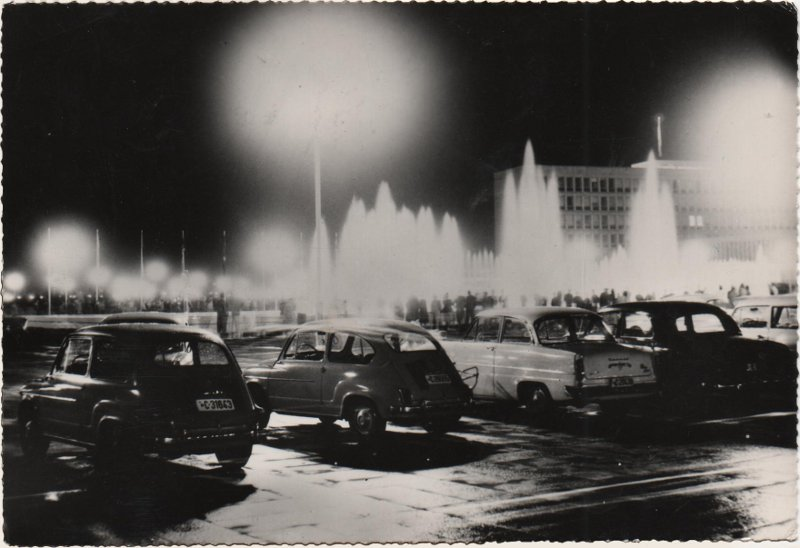 deckle edged black and white postcard showing parked motor cars at night
