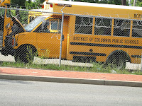 DCPS yellow school bus behind fence in parking lot with others