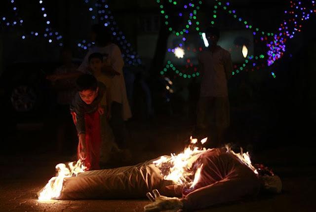 Индийский мальчик поджигает чучело, символизирующее уходящий 2013-й год. Снимок сделан в Мумбаи.