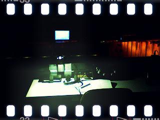 Filmstreifenbild: Dolmetscherkabine mit grünlichem Licht, rechts ein roter Vorhang, vorne die Leinwand