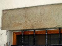 Detall de la llinda gravada i de la reixa de la finestra de l'antiga rectoria